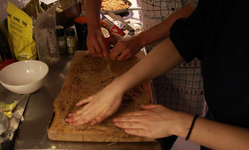 Image description: a messy kitchen work surface with four hands patting down a freshly made seitan dough.  Maria Guggenbichler & School in Common, Intimacy Manifesto, 2018. Photo: School in Common